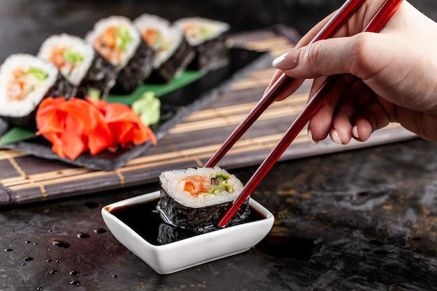 女の子は中華料理または日本料理の寿司を食べています。 Premium写真