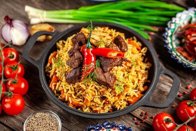木製テーブルの上に鋳鉄のフライパンで肉と国立ウズベキスタンのピラフ。 Premium写真