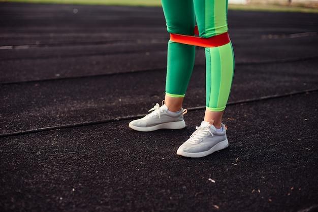 Ноги девушки в светло-зеленых леггинсах с розовой резинкой для тренировки на стадионе Premium Фотографии