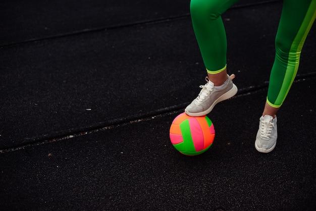 Ноги девушки в светло-зеленых леггинсах на ярком мяче, тренировка на стадионе, на улице. ноги согреют Premium Фотографии