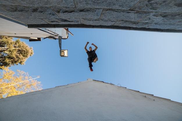 ある屋根から別の屋根への印象的なパルクールジャンプを行う若い男 Premium写真