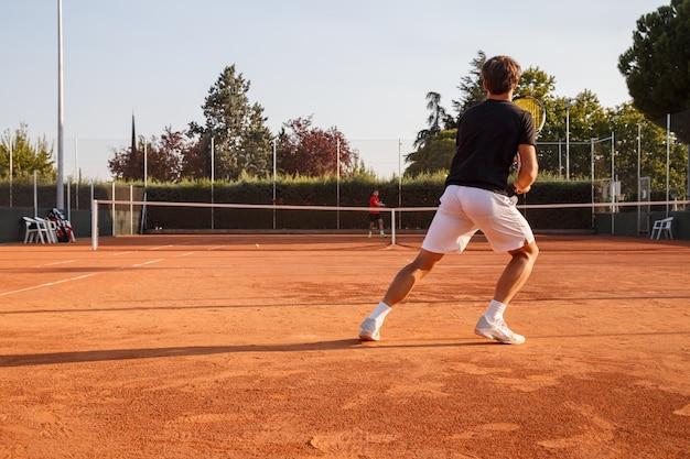 Профессиональный теннисист, играя в теннис на глины теннисный корт в солнечный день. Premium Фотографии