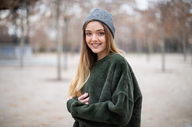秋の公園で冬の帽子と幸せな笑顔若いブロンドの女性の肖像画 Premium写真