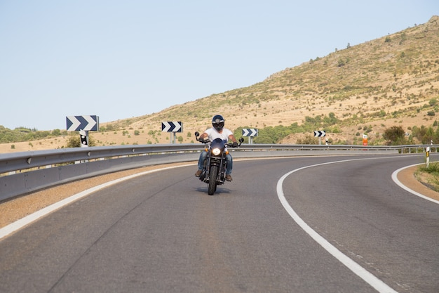 Молодой человек ехать мотоцикл на дороге в кривой в горах на солнечный день. Premium Фотографии