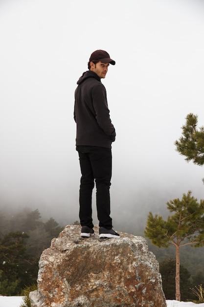 白人男性は、雪に覆われた山岳地帯の岩に登った。 Premium写真