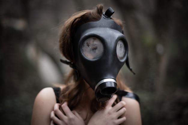 Анонимная женщина в черной одежде и противогазе в удивительном жутком лесу Premium Фотографии