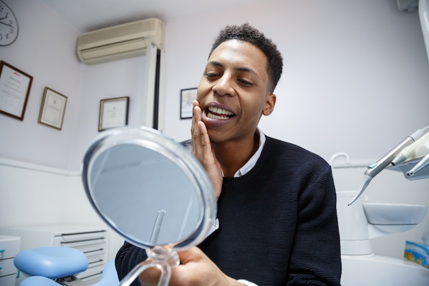 鏡を見て、歯科医の訪問中に不平を言いながら歯痛に苦しんでいるアフリカ系アメリカ人の男 Premium写真