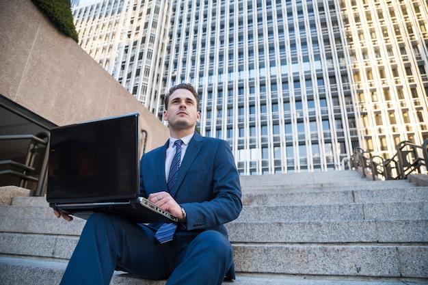 離れて見て膝の上のラップトップで階段でポーズエレガントなスーツの男を夢見ています。 Premium写真