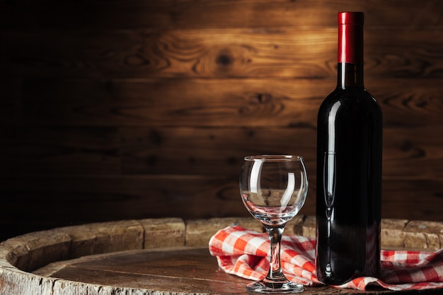 ボトルと木製の樽に赤ワインのグラス Premium写真