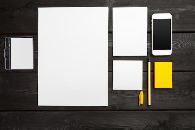 コーポレート・アイデンティティの空白のひな形は、スタイリッシュな黒の木製テーブルに設定します。ブランディング、ビジネスプレゼンテーション、ポートフォリオ。 Premium写真
