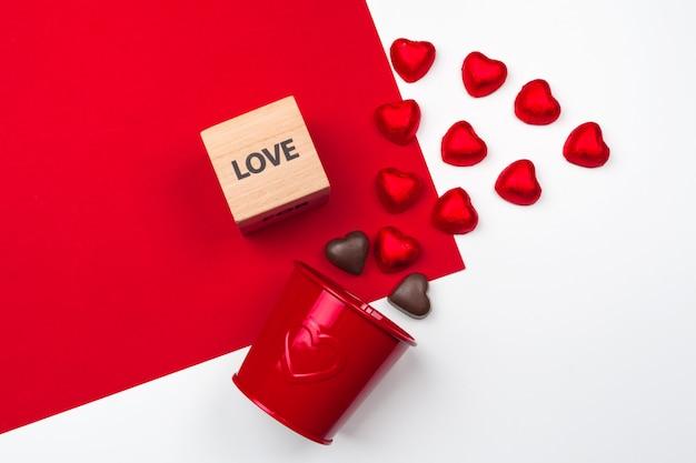 赤にチョコレートのハートのマグカップ。フラットレイアウト構成。ロマンチックな聖バレンタインの日 Premium写真