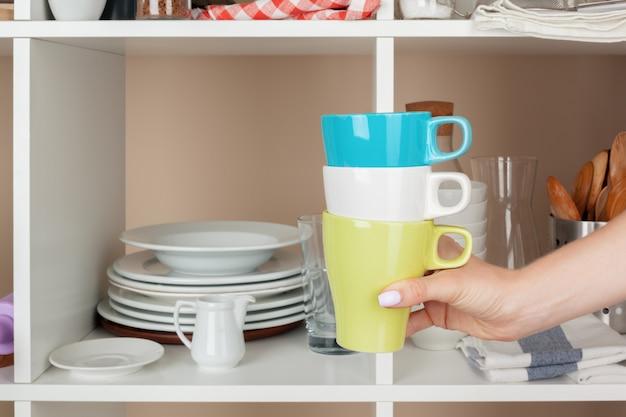 台所の棚から食器片を取る女性の手 Premium写真