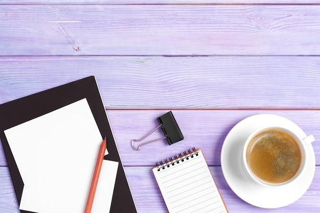Открытая тетрадь с чашкой кофе на деревянный стол Premium Фотографии
