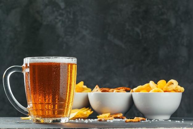 石のテーブルでラガービールとスナック。クラッカー、チップの側面図 Premium写真