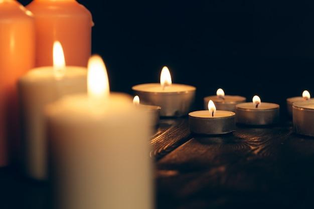 Свечи горят в темноте над черными. поминовение Premium Фотографии