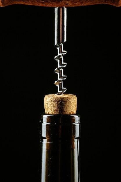 Штопор ввинчивается в пробку в бутылке вина Premium Фотографии