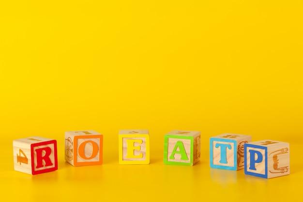 黄色の背景に文字でカラフルな木製ブロック Premium写真