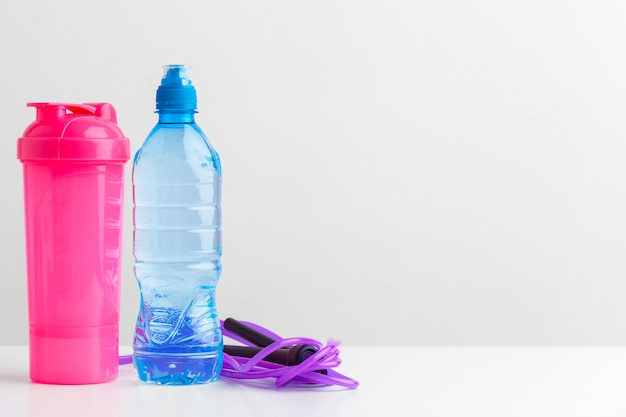 ワークアウトとリフレッシュメントのコンセプト。スポーツと健康。ボトルまたは縄跳びの近くの新鮮な水 Premium写真