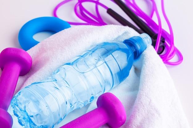 Концепция тренировки и отдыха. спорт и здоровье. бутылка или пресная вода возле скакалки Premium Фотографии