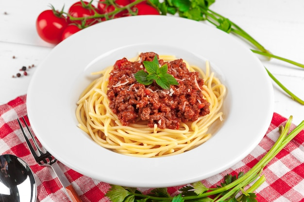 テーブルの上の肉、トマトソース、野菜のパスタ Premium写真