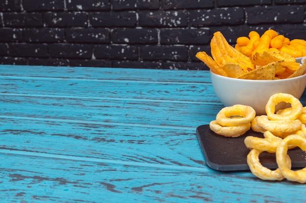 クラッカー、チップ、木製の表面の背景のクッキーのようなビールスナック Premium写真