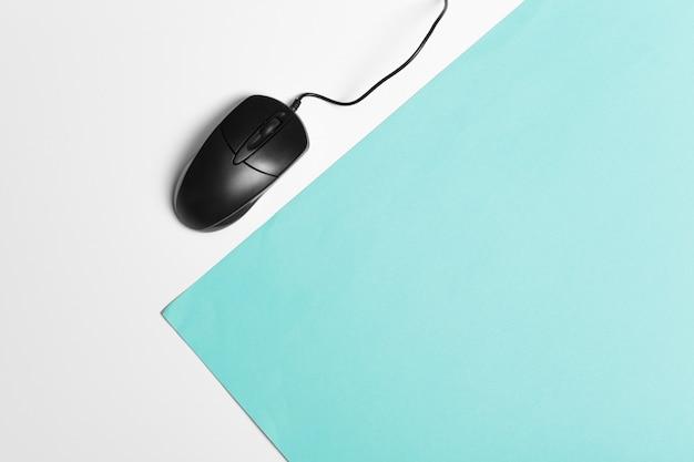 ターコイズブルーの紙の背景にコンピューターのマウス Premium写真
