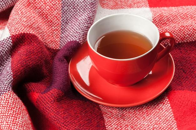 暖かい冬のニットスカーフに身を包んだ熱いお茶のカップ Premium写真