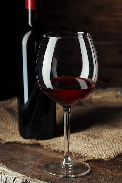 ボトルと木製の樽ショットに赤ワインのグラス Premium写真