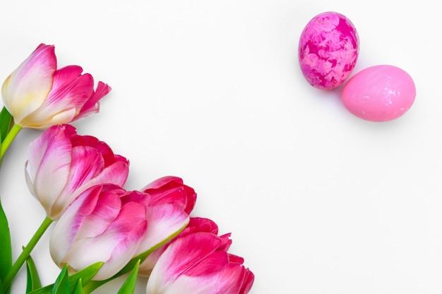 白い背景の上のチューリップの花とイースターエッグ Premium写真
