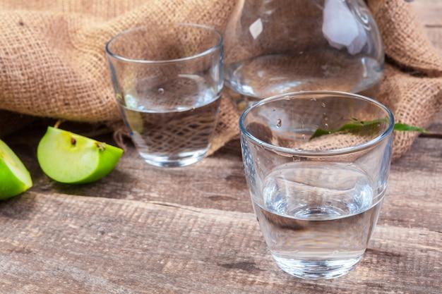 きれいな水と木製のテーブルに新鮮なリンゴのリンゴのスライスと食事のデトックスドリンクをクローズアップ Premium写真