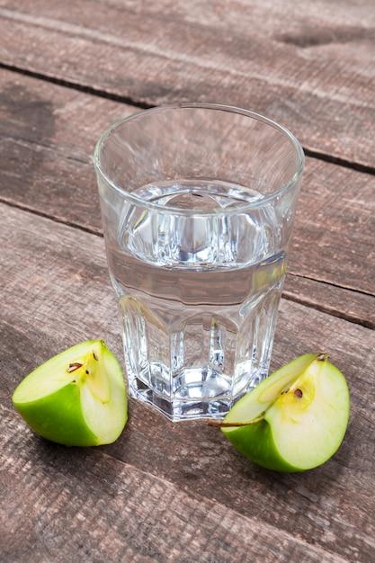 Диетический детокс напиток с кусочками яблок в чистой воде и свежее яблоко на деревянном столе, крупным планом Premium Фотографии