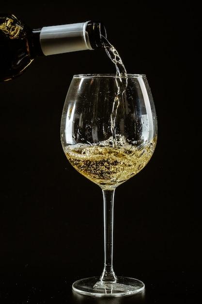 Белое вино наливают в бокал Premium Фотографии