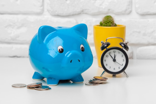 貯金箱は、コインと目覚まし時計、時間とお金の概念を保存します。 Premium写真