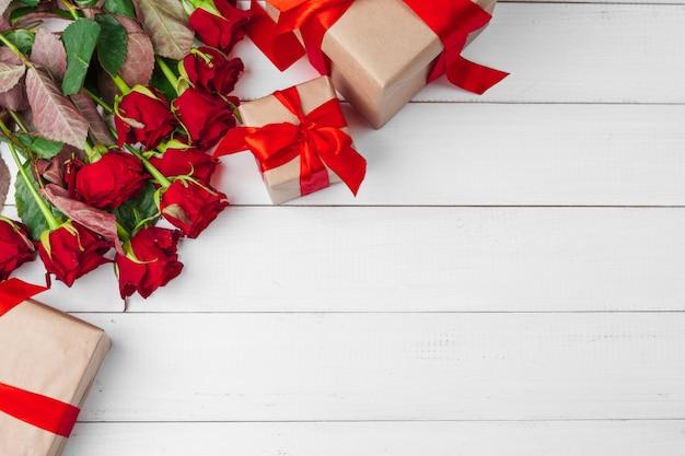 День святого валентина. красные розы и подарочная коробка на деревянном столе Premium Фотографии