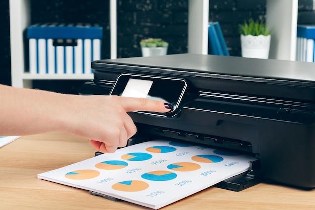 Женщина-секретарь делает ксерокопии на аппарате ксерокса в офисе Premium Фотографии