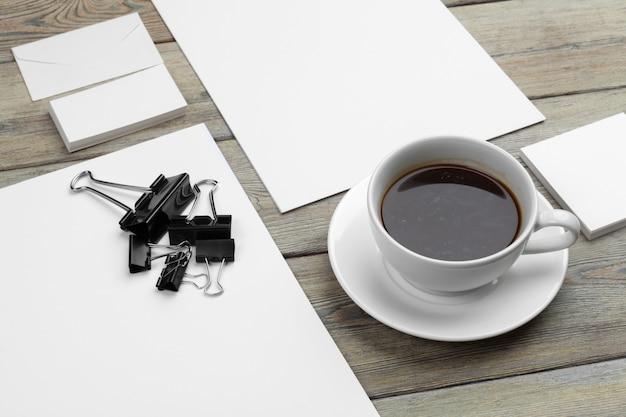 名刺、ノート、紙の文書、コーヒーカップのモックアップセット。 Premium写真