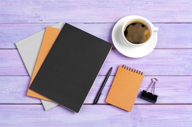 木製の机の上のコーヒーカップでノートブックを開く Premium写真