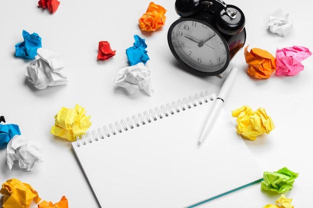 しわくちゃの紙のボールとメモ帳付き目覚まし時計 Premium写真