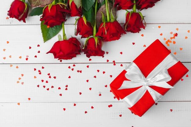 赤いバラと木製のテーブルの上のギフトボックス Premium写真