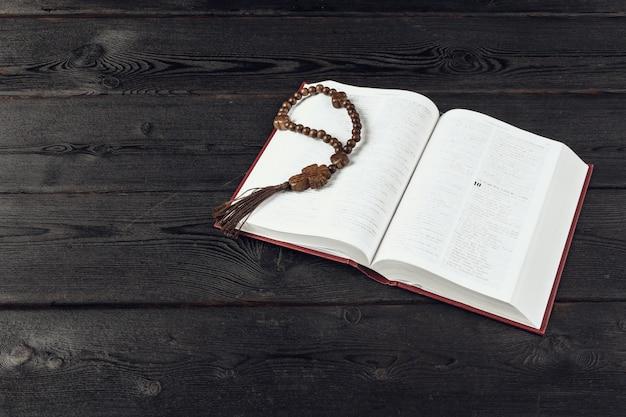 聖書と古い木製のテーブルに十字架 Premium写真