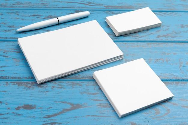 青い机の上の文房具のブランディング。紙、名刺、パッド、ペン、コーヒーの平面図。 Premium写真