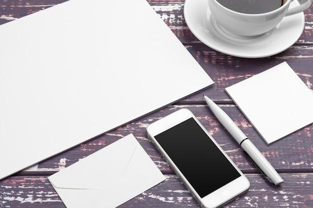紫色の机の上の文房具の実物大模型。紙、名刺、パッド、ペン、コーヒーの平面図。 Premium写真