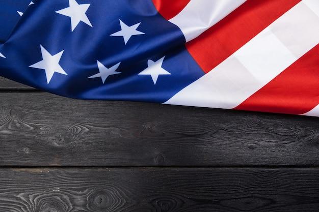 暗い木製のテーブルにアメリカ国旗 Premium写真