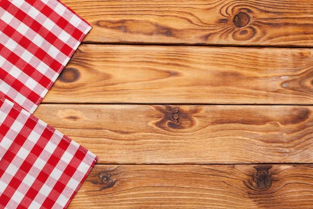 Клетчатая скатерть на деревянной поверхности стола Premium Фотографии