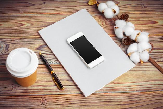 Сотовый телефон и филиал цветок хлопка на столе. вид сверху. Premium Фотографии