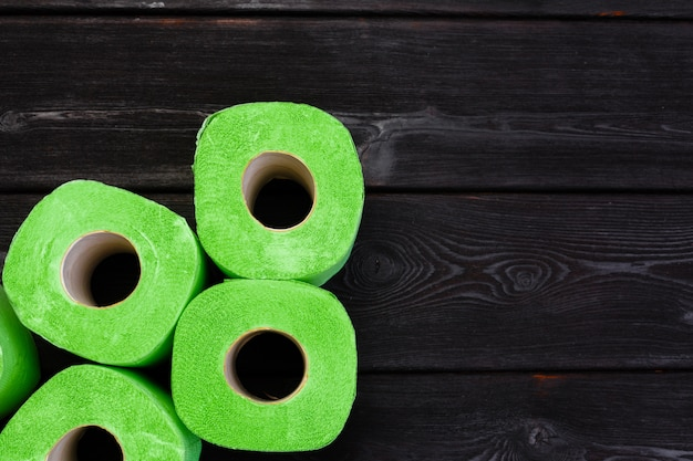 Зеленые рулоны туалетной бумаги на черном деревянном столе Premium Фотографии