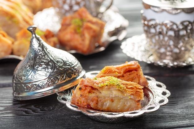 トルコのアラビア語のデザートバクラヴァ、ハチミツとシルバープレートのナッツ Premium写真
