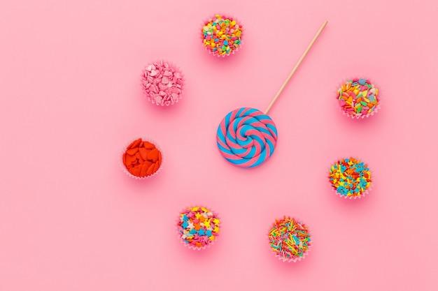 ピンクの背景、トップビューでペーパーボウルにロリポップと砂糖を振りかける Premium写真