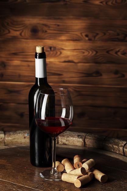 ボトルと暗い背景の木で撮影した木製の樽に赤ワインのグラス Premium写真