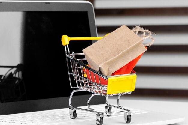 オンラインショッピングの概念。ショッピングカート、机の上のノートパソコン Premium写真